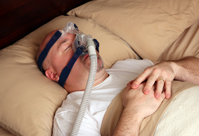 Man sleeping while wearing equipment used for our sleep apnea treatment in Burley, ID